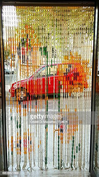 Car On Street Seen From Beaded Curtain On Doorway
