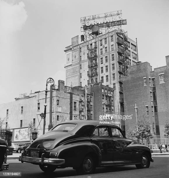 Car on the corner of Henry Street and Rutgers Street in the Lower East Side of Manhattan, New York City, with the Jewish Daily Forward Building in...
