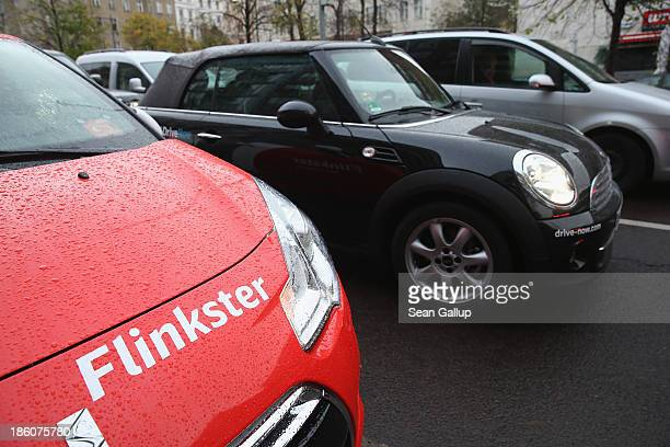Car operated by the Flinkster car-sharing company stands parked as a car from its competitor Drive Now drives past on October 28, 2013 in Berlin,...