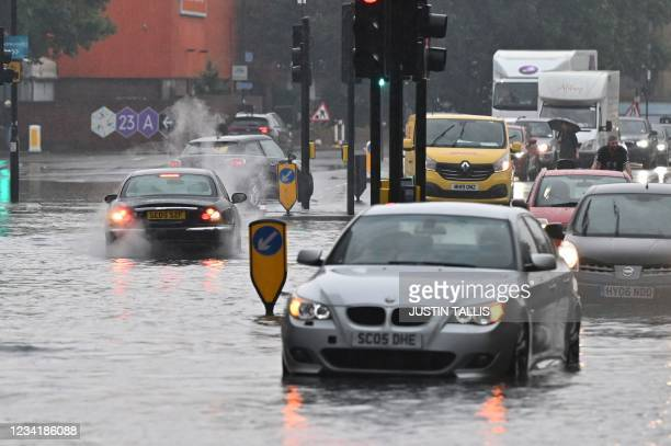 Car overheats on a flooded road in The Nine Elms district of London on July 25, 2021 during heavy rain. - Buses and cars were left stranded when...