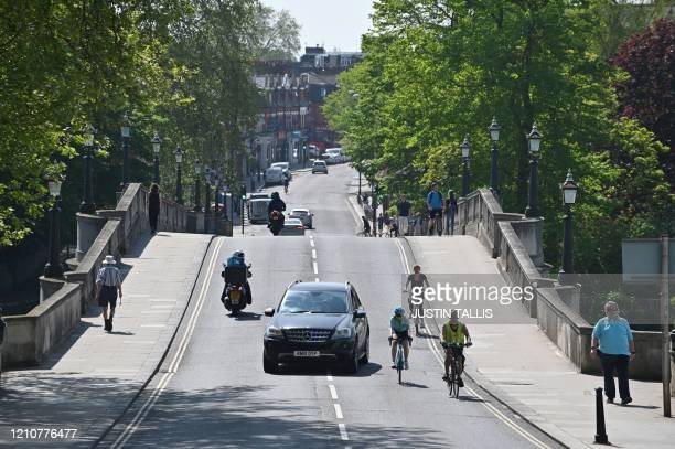 Car overtakes cyclists in Richmond, south west London on April 23, 2020 during the lockdown aimed at halting the spread of the novel coronavirus...