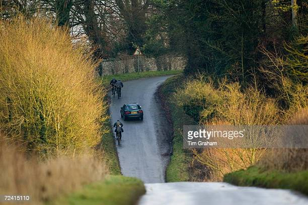 Car overtakes cyclists on country road near Burford, United Kingdom.