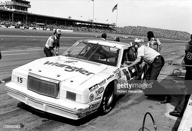 NASCAR car owner Bud Moore talks with his driver Dale Earnhardt Sr during a pit stop during the 1982 Firecracker 400 at the Daytona International...