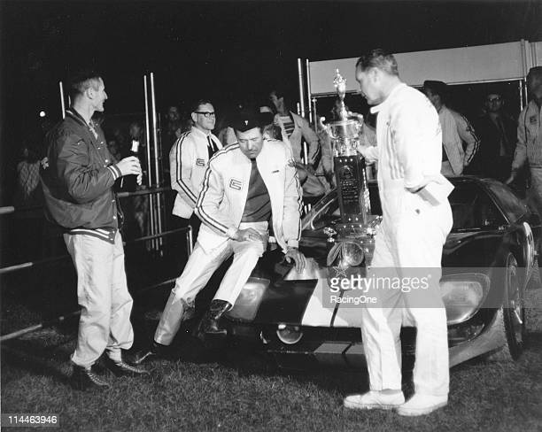 Car owner Carroll Shelby sits on the front of his Ford GT-40 after drivers Ken Miles and Lloyd Ruby drove the car to victory in the Daytona...