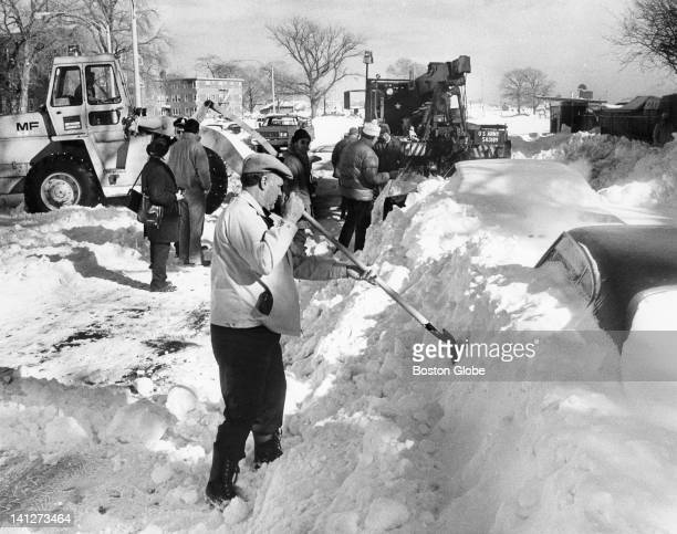 Car owners MDC workers and the National Guard dig out cars buried in snow on Day Boulevard in South Boston after the blizzard of 1978