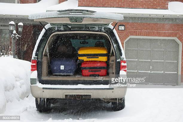 Car packed with suitcases in snow