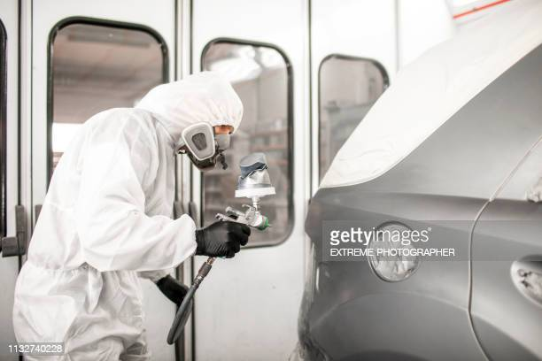 Car painter in white overalls spraying a car body with paint