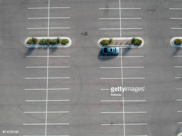 A car parked at a large parking lot.