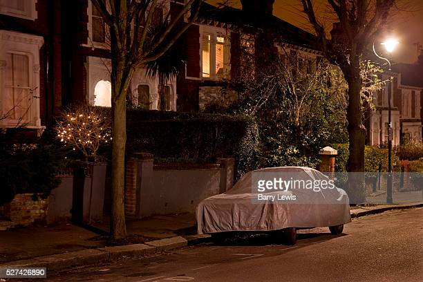 Car parked at night on a London street covered in protective wrapping to protect it against theft and bad weather