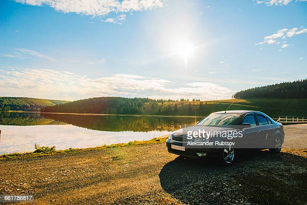 car parked by lake on rolling landscape - 固定された ストックフォトと画像