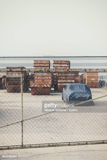 car parked by stack of containers seen through fence - albrecht schlotter stock photos and pictures
