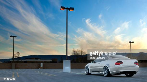 car parked in empty parking lot - car park stock pictures, royalty-free photos & images