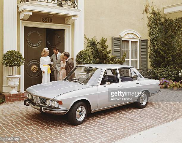 Car parked in front of house, couple standing at entrance door