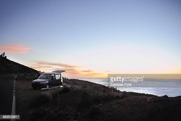 car parked near road above clouds in mountains - landfahrzeug stock-fotos und bilder