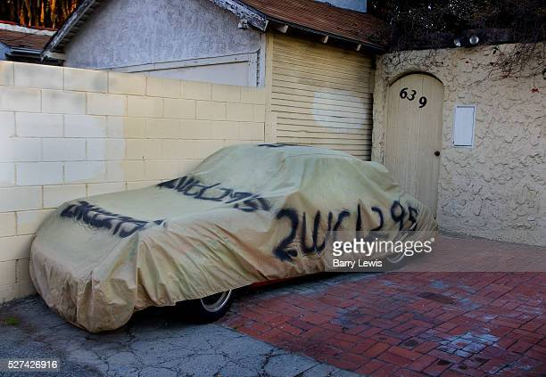 Car parked on a Los Angeles alley covered in protective wrapping to protect it against theft and bad weather The plate number is sprayed on the cover...