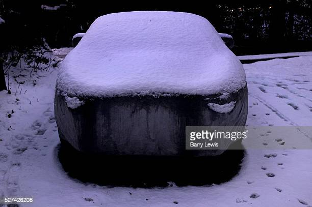 Car parked on a snow covered drive off a London street covered in protective wrapping to protect it against theft and bad weather