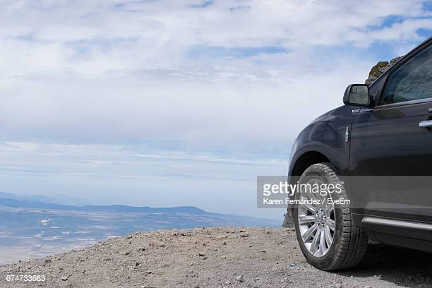 Car Parked On Cliff Against Sky