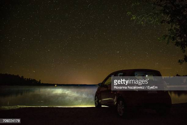 Car Parked On Lakeshore Against Starry Sky At Night