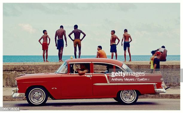 car parked on road against friends standing on retaining wall at beach - cuba photos et images de collection
