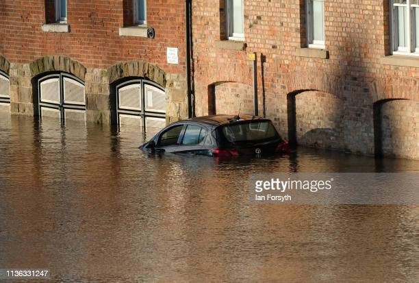 A car parked overnight is caught out as river waters rise and spill over the banks of the River Ouse on March 17 2019 in York England Heavy rain...