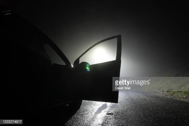 a car parked, with door open, on the side of the road, underneath a street light. on a foggy winters night - crime stock pictures, royalty-free photos & images