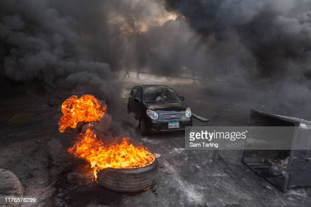 Car passes a barricade as protesters burn tyres to block a highway in Beirut, Lebanon during unrest sparked by economic difficulties on October 18,...