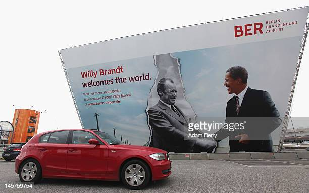 A car passes a billboard advertising the new Berlin Brandenburg Airport at Tegel airport on June 5 2012 in Berlin Germany Due to the delayed opening...