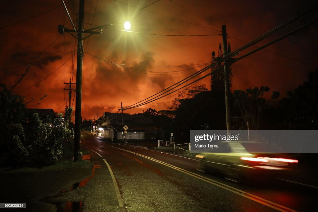 A car passes as lava from a Kilauea volcano fissure illuminates the night sky, after midnight on Hawaii's Big Island, on May 27, 2018 in Pahoa, Hawaii. Pahoa and surrounding areas have been hard hit by the recent Kilauea eruptions. The Big Island, one of eight main islands that make up Hawaii state, is struggling with tourist bookings following the Kilauea volcano eruptions, with summer bookings down 50 percent. Officials stress that the eruptions have thus far only affected a small portion of the island. Visitors spent $2.4 billion at the island in 2017.
