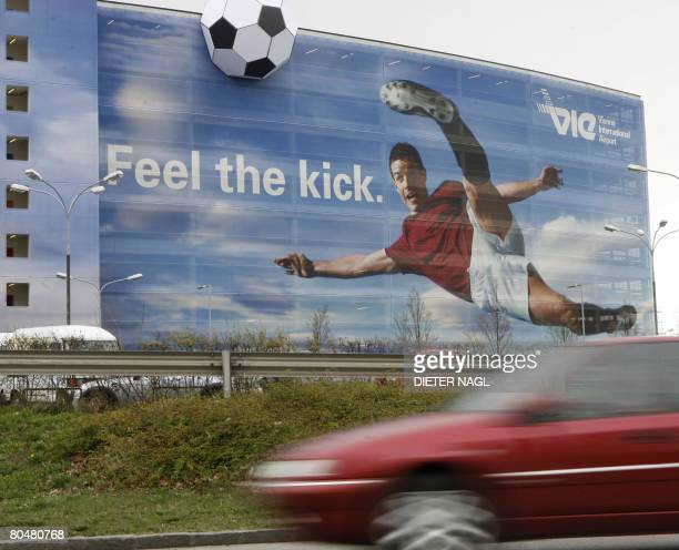 A car passes by a multistorey car park which is coverd with a giant poster of a football player to welcome guests for the UEFA EURO 2008 at the...