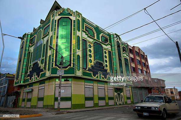 """Car passes by a recently constructed building known locally as a """"cholet,"""" for its incorporation of indigenous architecture, in El Alto, Bolivia, on..."""