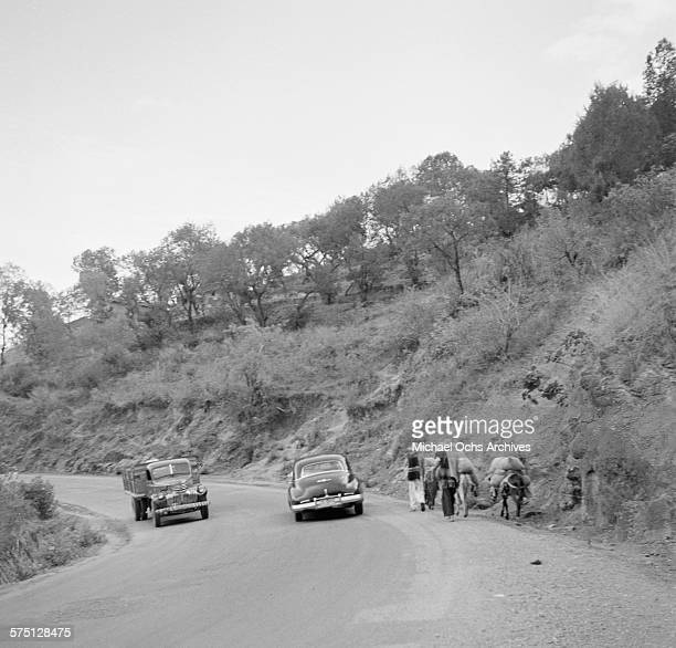 A car passes locals with their pack donkeys on the side of the roadway in Cuernavaca Mexico