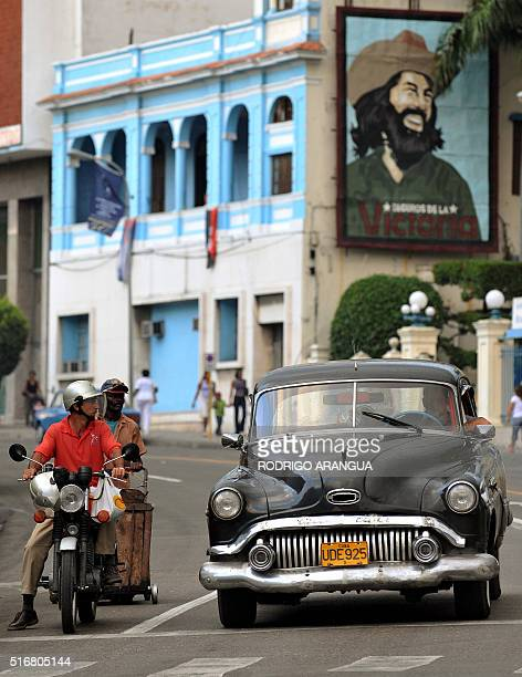 A car passes next to a banner of Cuban revolutionary leader Camilo Cienfuegos in downtown Santiago de Cuba on December 30 2008 Next January 1 2009...