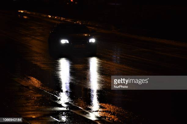 A car passes through a raindrenched road illuminated by the headlights during a heavy rainfall in Ankara Turkey on November 30 2018 Torrential...
