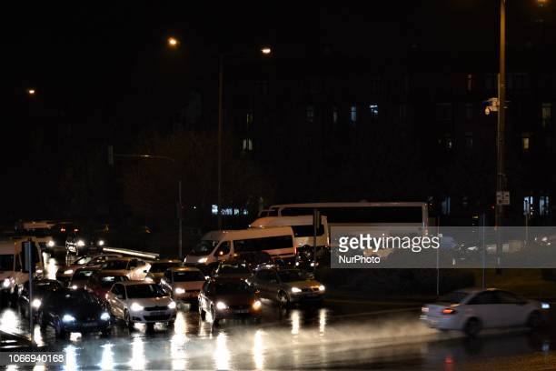 A car passes through a raindrenched road while another cars stop at an intersection during a heavy rainfall in Ankara Turkey on November 30 2018...