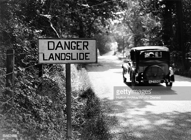 Car passing 'Danger Landslide' sign  (B&W)