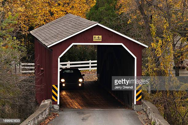 a car passing through a covered bridge - covered bridge stock pictures, royalty-free photos & images