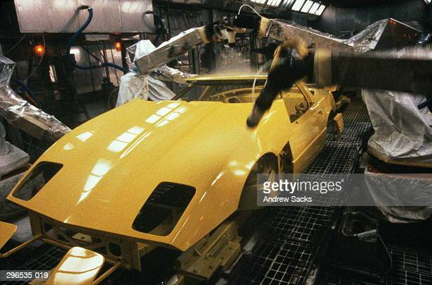 Car plant production line,robots spraying Corvette with yellow paint