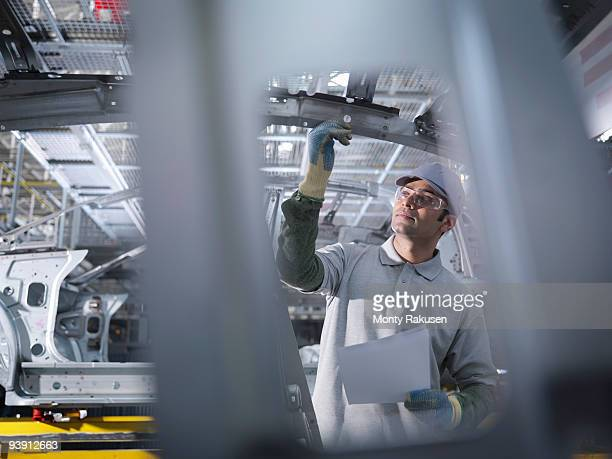 Car Plant Worker Inspecting Car