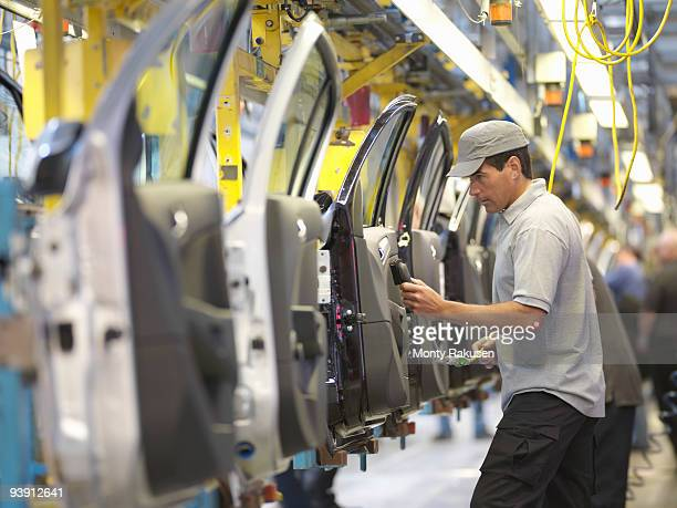 car plant worker on production line - motor vehicle stock photos and pictures