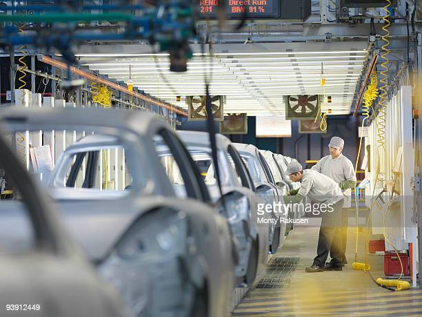 car plant workers on production line - production line stock pictures, royalty-free photos & images