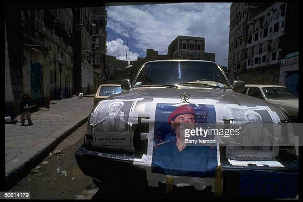 Car plastered w campaign posters incl imaging Pres Ali Abdullah Saleh during parliamentary elections