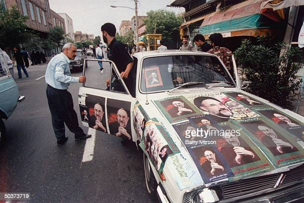 Car plastered w. Posters picturing surprise front-runner presidential candidate, moderate cleric Mohammed Khatami, parked on street during election...