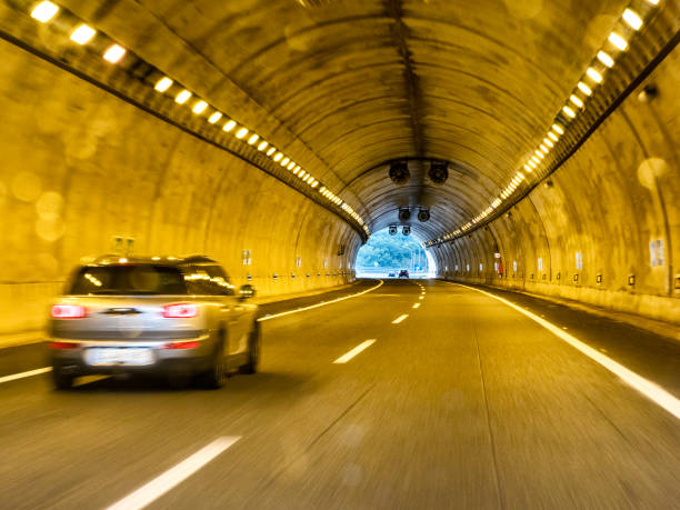 Car point of view driving, cars moving through a lighted tunnel on a highway.