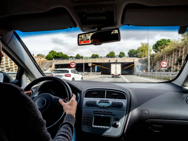 Car point of view, young man drives a car on a rainy highway and approaches a tunnel entrance.