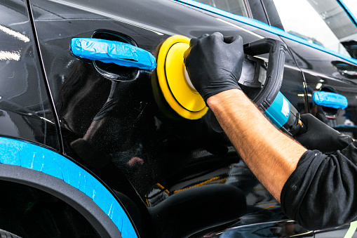 Car polish wax worker hands applying protective tape before polishing. Buffing and polishing car. Car detailing. Man holds a polisher in the hand and polishes the car 1060499948