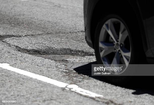 A car prepares to drive over a pothole on May 15 2017 in San Francisco California San Francisco mayor Ed Lee announced a twoyear $90 million street...