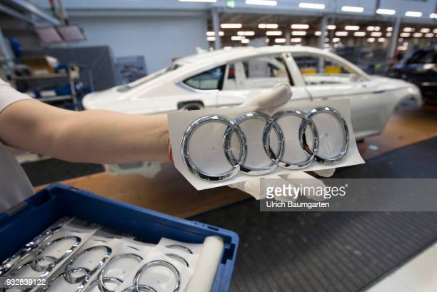 Car production at Audi AG in Ingolstadt The hand of a worker with the Audi logo in front of the car production line