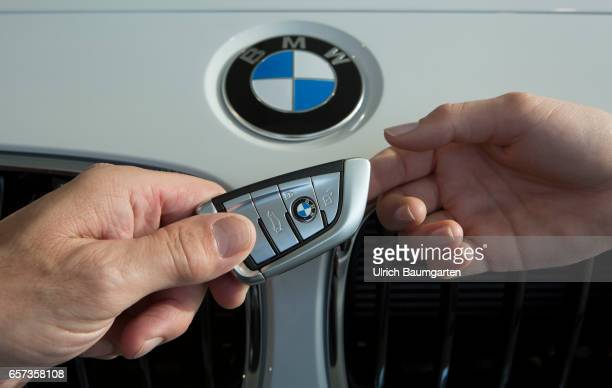 Car purchase the symbol photo shows the hand of a seller with a BMW car key and the hand of a buyer during the vehicle handover in front of the BMW...