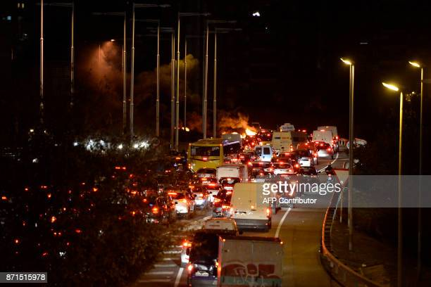 Car queue as a fire burns at a picket on the Ronda de Dalt road in Barcelona during a general strike to protest the jailing of eight sacked regional...