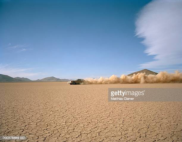 Car racing through desert, side view